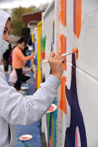 Une jeune fille peint sur le mur du stade