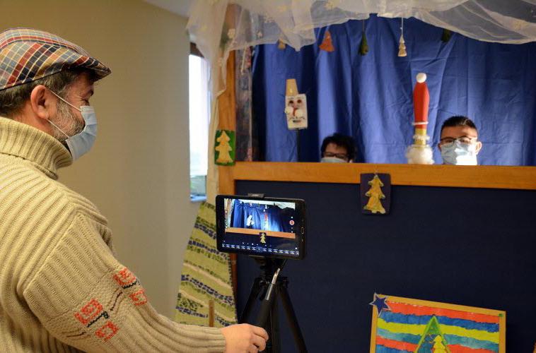 un homme fait une vidéo d'un théâtre de marionnettes