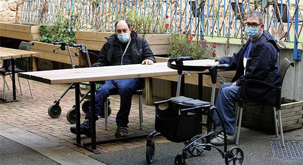 Deux personnes avec des masques autour d'une table